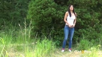 Sassy blonde female in denim pants Rebecca pees within the forest