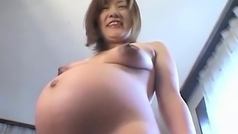Far eastern preggo plays with her tits