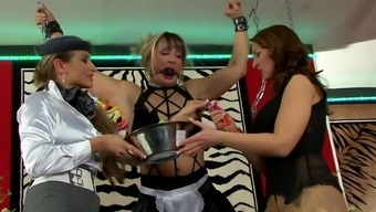 Femdom lesbian threesome with the use of chained brown